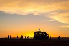 Touristes appréciant un coucher du soleil à côté du camion dans le désert d'Atacama Photo stock