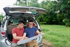 Touristes asiatiques employant la carte de papier Images stock