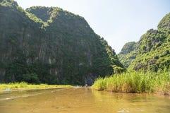 Touristes Asie voyageant dans le bateau le long de la nature la rivière et le bâti Photo libre de droits