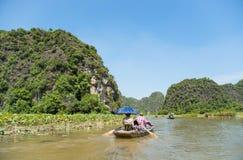 Touristes Asie voyageant dans le bateau le long de la nature la rivière et le bâti Photos stock