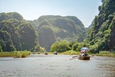 Touristes Asie voyageant dans le bateau le long de la nature la rivière et le bâti Photographie stock libre de droits