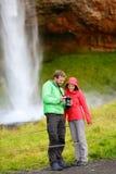 Touristes avec l'appareil-photo de SLR par la cascade sur l'Islande Photographie stock libre de droits
