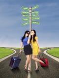 Touristes avec un poteau indicateur de destination de voyage Image libre de droits