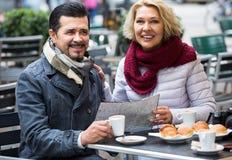 Touristes ayant le café au café et lisant la carte Photo libre de droits