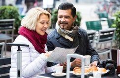 Touristes ayant le café au café et lisant la carte Photos libres de droits