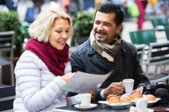 Touristes ayant le café au café et lisant la carte Photo stock
