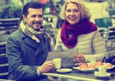 Touristes ayant le café au café et lisant la carte Image libre de droits
