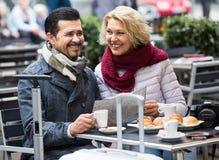 Touristes ayant le café au café et lisant la carte Images stock