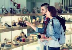 Touristes choisissant des chaussures de l'étalage Photo libre de droits