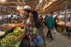 Touristes choisissant des légumes sur les produits de achat asiatiques traditionnels des jeunes du marché dans le bazar Images stock