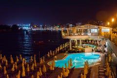 Touristes détendant près d'une piscine la nuit photographie stock