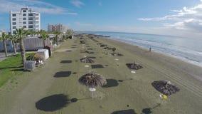 Touristes détendant sur la plage avec des parasols de paille, tir aérien, ville de Larnaca clips vidéos