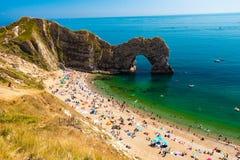 Touristes détendant sur la plage de porte de Durdle, Dorset image stock