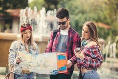 Touristes d'amis avec la carte en parc Image stock