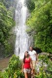Touristes d'Hawaï trimardant par la cascade Photographie stock