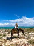 Touristes d'?quitation au Cuba Fille sur un cheval sur une plage photographie stock libre de droits