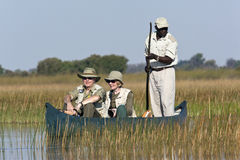 Touristes dans le delta d'Okavango - Botswana Photographie stock libre de droits