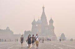 Touristes dans le masque de gaz sur le grand dos rouge sous le brouillard enfumé Images stock