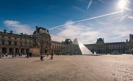 Touristes dans les cours centrales de l'auvent avec la pyramide et le palais de Louvre Image stock