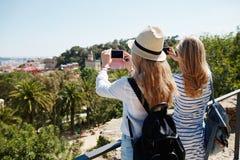 Touristes de couples prenant le paysage de photo avec le téléphone d'appareil-photo sur le parc Photographie stock libre de droits
