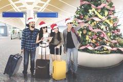 Touristes de diversité avec le chapeau de Santa à l'aéroport Photographie stock