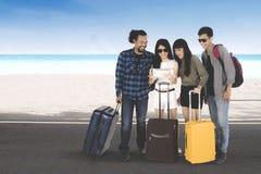 Touristes de diversité avec un comprimé sur la plage Photo stock
