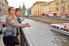 Touristes de filles à la porte du remblai de canal de Griboyedov dedans photographie stock libre de droits
