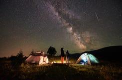 Touristes de mère et de fils se reposant au camping en montagnes au ciel nocturne complètement des étoiles et de la manière laite Images stock