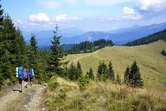 Touristes de personnes trimardant en montagnes, voyageant Image stock