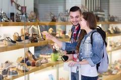 Touristes de sourire achetant des chaussures Photos stock