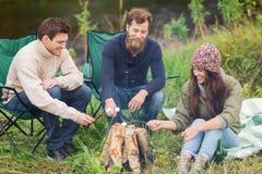 Touristes de sourire faisant cuire la guimauve dans le camping Photos stock