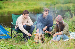 Touristes de sourire faisant cuire la guimauve dans le camping Images libres de droits