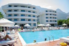 Touristes de vacances autour de la piscine par temps chaud image stock