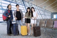 Touristes divers se tenant avec des valises à l'aéroport Photo libre de droits