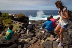 Touristes donnant sur le geyser de mer en île d'Espanola Images stock