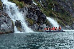 Touristes du bateau de croisière près des cascades du glacier Nena Image stock