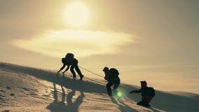 Touristes escaladant une falaise de neige de montagne Étirage d'un coup de main aide de personnes Travail d'équipe, concept de tr clips vidéos