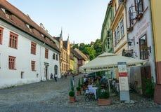 Touristes et maisons sur des rues de la ville médiévale de Sighisoara, Roumanie Bâtiments et cafés antiques de rue photographie stock