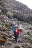 Touristes et portiers sur le chemin à Kilimanjaro Image libre de droits