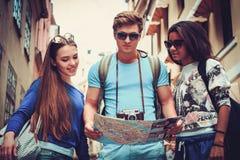 Touristes ethniques multi d'amis avec la carte dans la vieille ville Photographie stock libre de droits