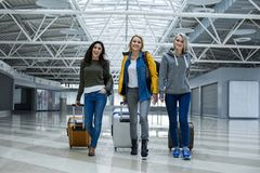 Touristes féminins satisfaisants avec des cas se déplaçant vers le jet Photographie stock libre de droits