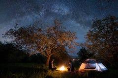 Touristes heureux de couples s'asseyant à un feu de camp près de la tente sous des arbres et du beau ciel nocturne complètement d Images stock