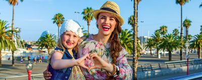 Touristes heureux de mère et de fille montrant les mains en forme de coeur Images libres de droits