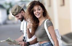Touristes heureux faisant un tour dans une rue de ville dans un jour ensoleillé Photographie stock