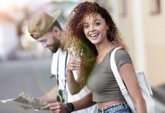 Touristes heureux faisant un tour dans une rue de ville dans un jour ensoleillé Photos stock