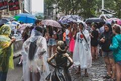 Touristes heureux prenant des photos avec la statue courageuse de fille à Manhattan inférieure, dans un jour pluvieux photos stock
