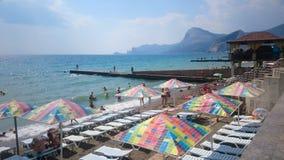 Touristes heureux prenant un bain de soleil et nageant en Mer Noire, vue de plage de Sudak clips vidéos
