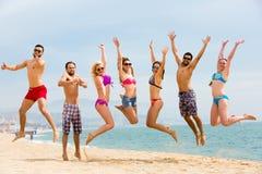 Touristes heureux sautant sur la plage Image libre de droits
