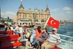 Touristes heureux sur un ferry à travers le Bosphorus observant Istanbul historique Photographie stock