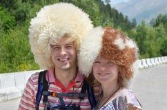 Touristes heureux utilisant les chapeaux drôles de moutons se tenant sur la montagne roa Photo libre de droits
